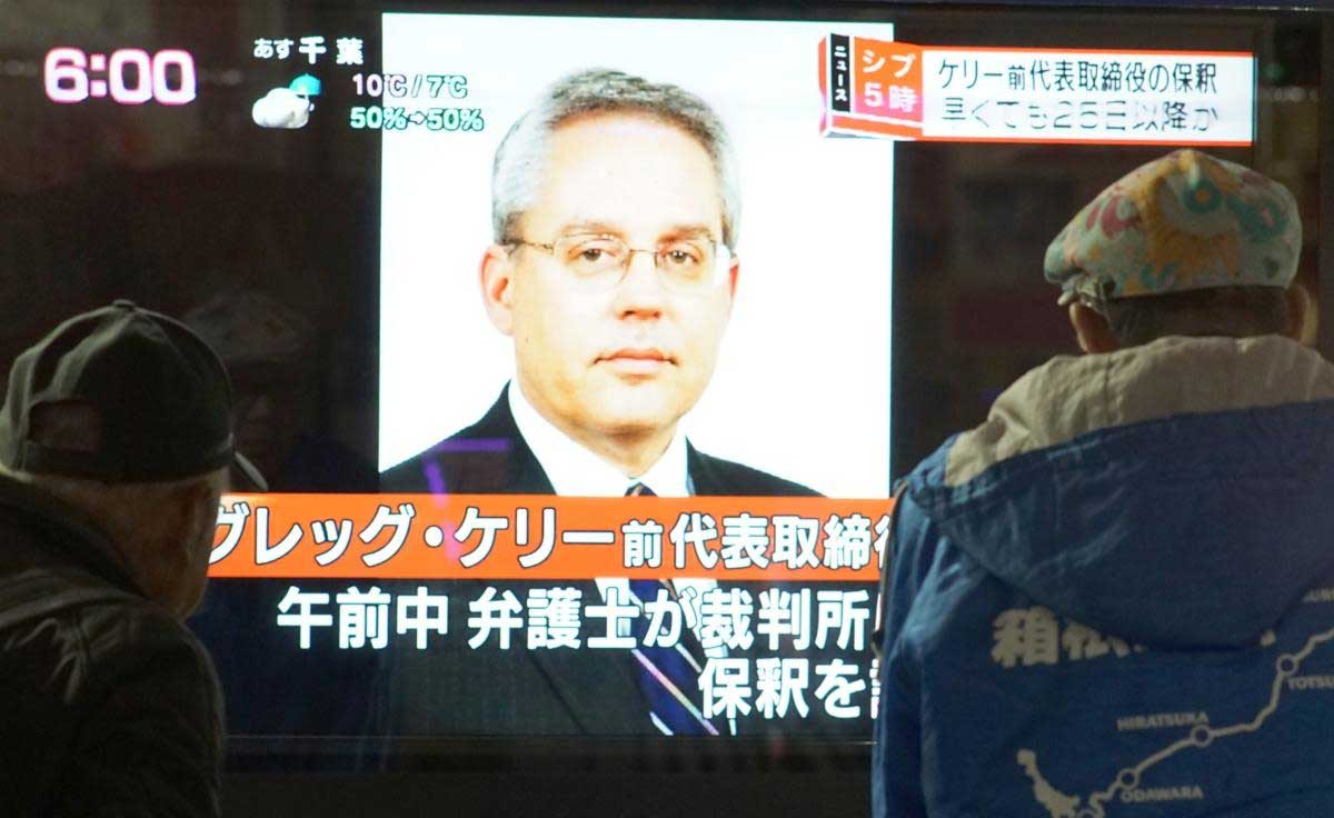 This picture taken on December 21, 2018 shows pedestrians looking at a television news program featuring former former Nissan representative director Greg Kelly in Tokyo. - Japanese authorities suspect former Nissan boss Carlos Ghosn conspired with his right-hand man Kelly to hide away around half of his income (some five billion yen or $44 million) over five fiscal years from 2010. (AFP Photo)