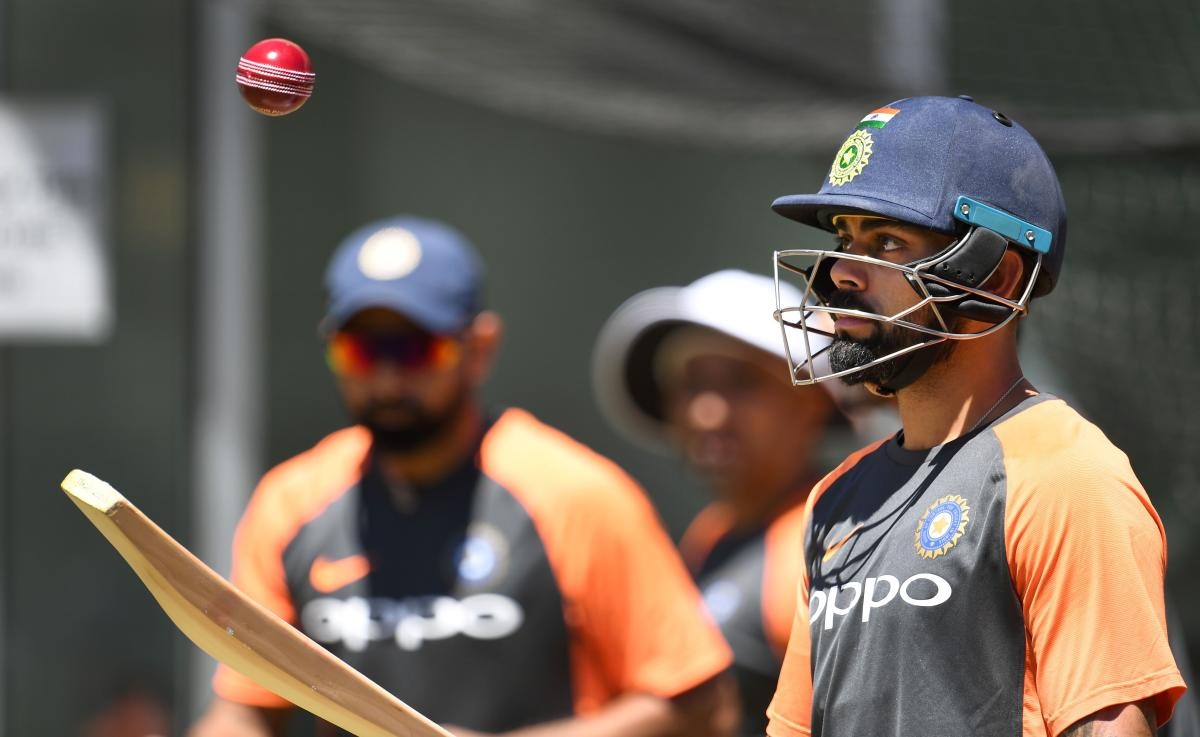 India's captain Virat Kohli (R) hits a ball in the air during a training session in Melbourne on December 24, 2018, ahead of the third cricket Test match against Australia. (AFP Photo)