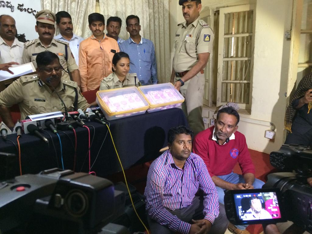 Police Commissioner D C Rajappa giving information about fake currency seized in Belagavi on Tuesday. Accused are seen sitting.