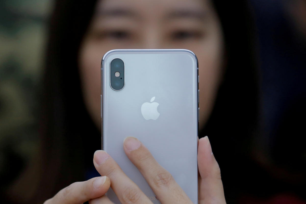 An attendee uses a new iPhone X during a presentation for the media in Beijing, China, on October 31, 2017. REUTERS