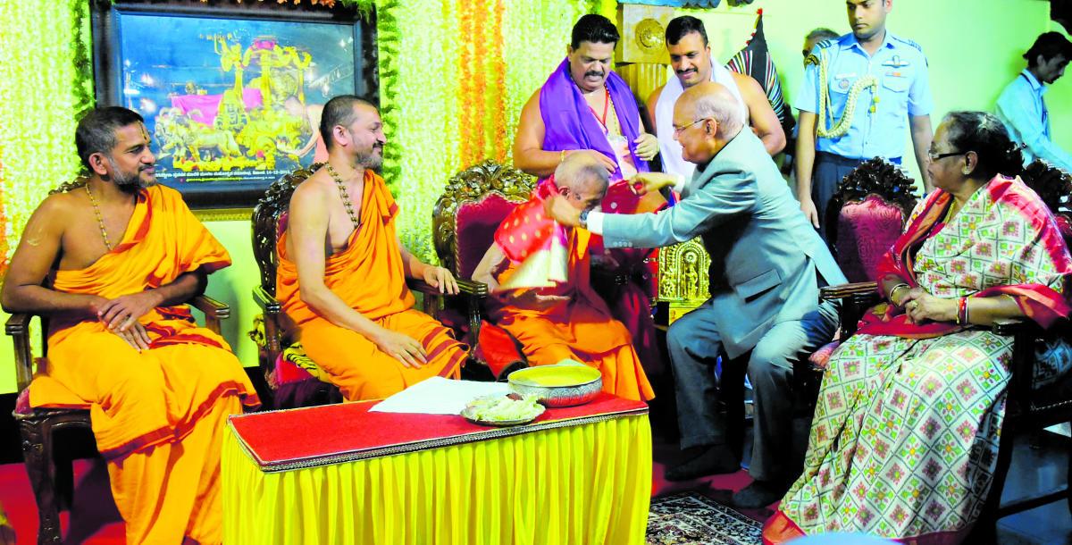The President Ram Nath Kovind felicitates Pejawar Mutt Pontiff Vishwesha Teertha Swami, who completed 80 years of asceticism, in Udupi on Thursday.