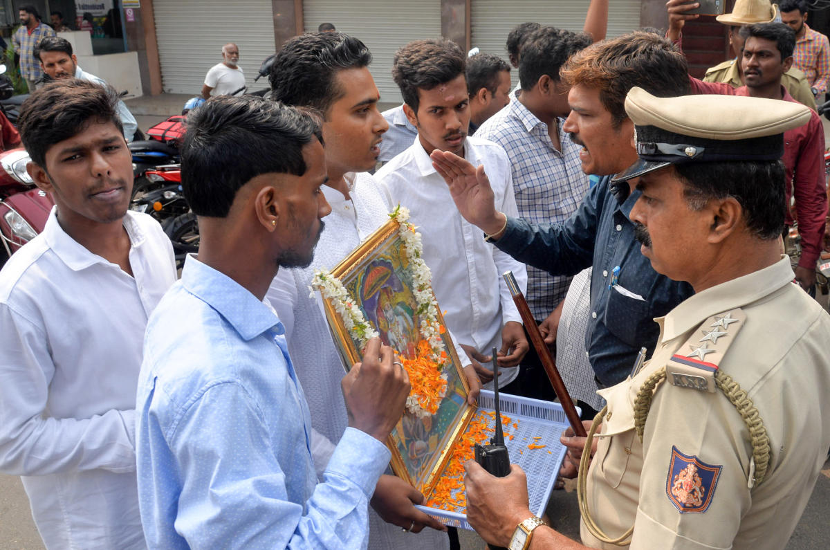 Police prevent BJP Yuva Morcha members, led by Nishanth, from staging a protest with a photograph of Lord Rama in front of rationalist-writer K S Bhagawan's residence in Mysuru on Friday. DH photo