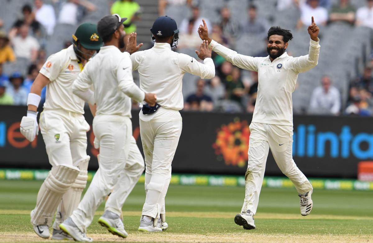 India's Ravindra Jadeja (R) celebrates taking a wicket of Australia's batsman Marcus Harris (L) with teammates during day four of the third cricket Test match between Australia and India in Melbourne on December 29, 2018. (AFP Photo)