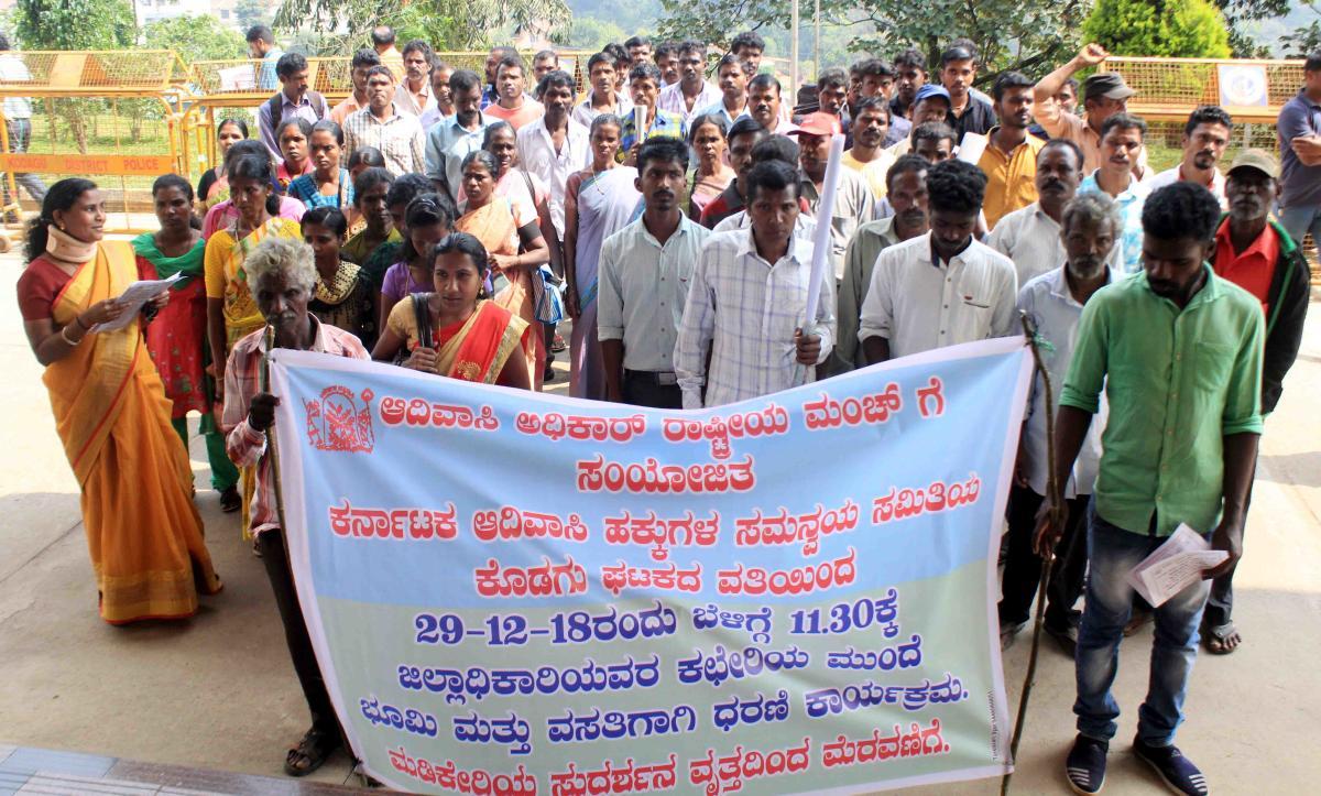 Members of Karnataka Adivasi Hakkugala Samanvaya Samithi stage a protest in Madikeri on Saturday.