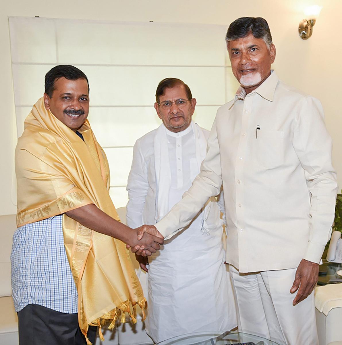 Chief Minister of Andhra Pradesh Nara Chandrababu Naidu greets his Delhi counterpart Arvind Kejriwal as Sharad Yadav looks on, in New Delhi, on Saturday. PTI