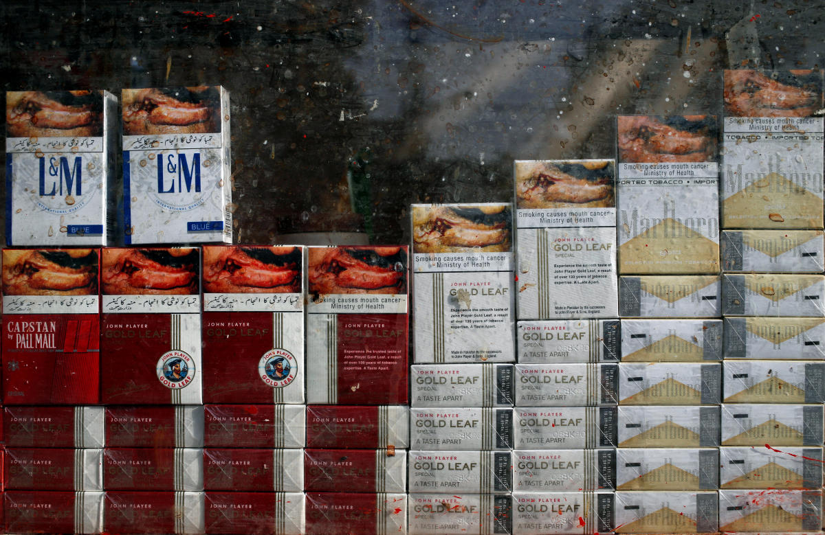 Stack of cigarette packs with health warnings displayed in a showcase of a kiosk along a street in Karachi, Pakistan May 5, 2018. Picture taken May 5, 2018. REUTERS/Akhtar Soomro
