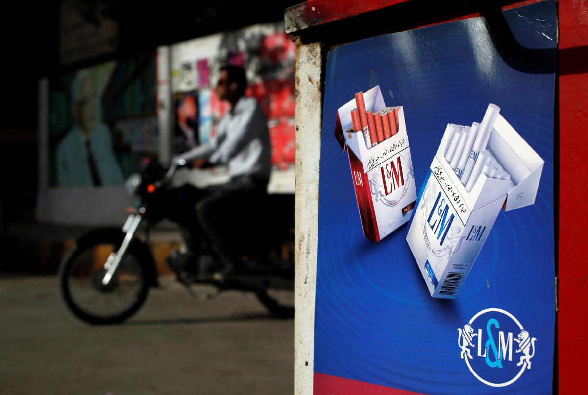 A commuter rides his bike past a sign depicting advertisement of L&M cigarettes, which is the brand of Philip Morris, at a kiosk along a road in Karachi, Pakistan May 5, 2018. Picture taken May 5, 2018. REUTERS/Akhtar Soomro