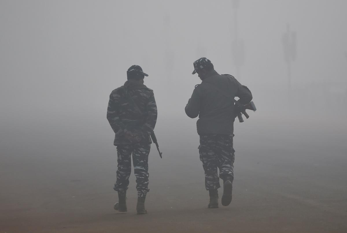 Indian security forces walk amid heavy fog and smog conditions in New Delhi on January 3, 2019. (Photo by Money SHARMA / AFP)