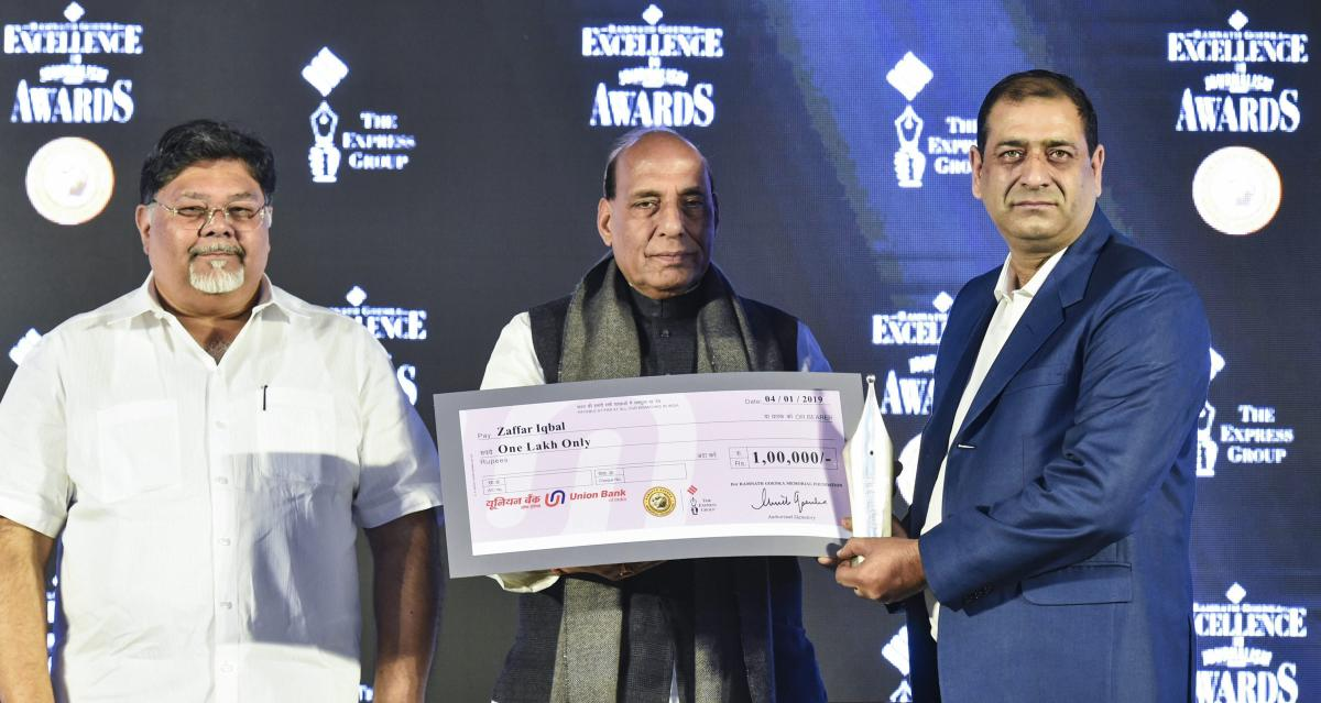 Home Minister Rajnath Singh presents a cheque to TV journalist Sheikh Zafar Iqbal as Indian Express Group MD Viveck Goenka looks on during the 13th edition of Ramnath Goenka Excellence in Journalism Awards, in New Delhi. PTI photo