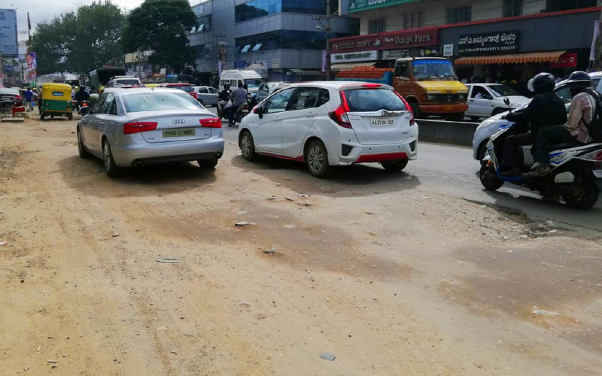 The Hennur-Bagaluru Road at Hennur Cross. The digging has shrunk the tarred road resulting in traffic pile-up. (DH Photo)