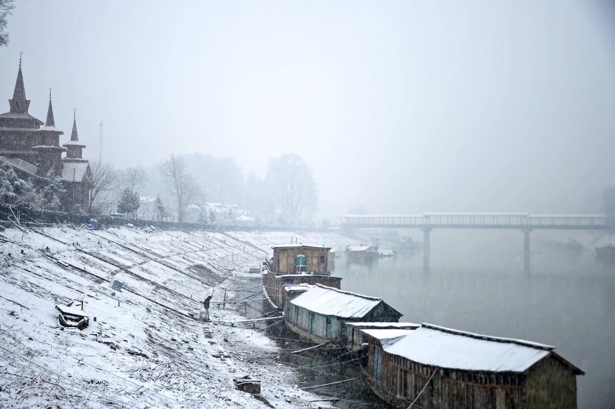 Houseboats covered by snow are seen along the banks of Jehlum river during a snowfall in Srinagar on January 4, 2019. (AFP Photo)