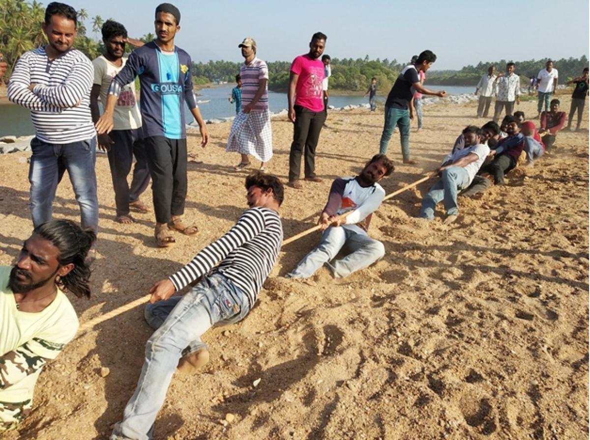 Men take part in tug of war held as a part of the Beach Utsav at Kalihithlu in Shiroor.