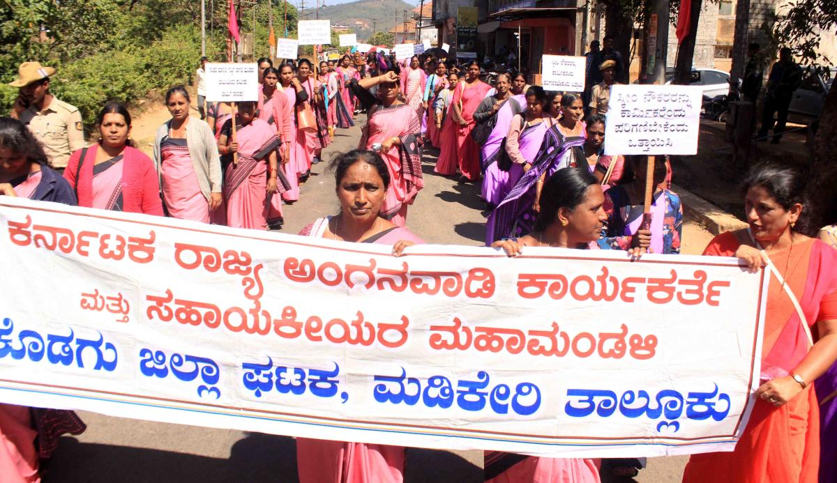 Members of Labourers Joint Action Committee take out a protest rally in Madikeri on Wednesday.