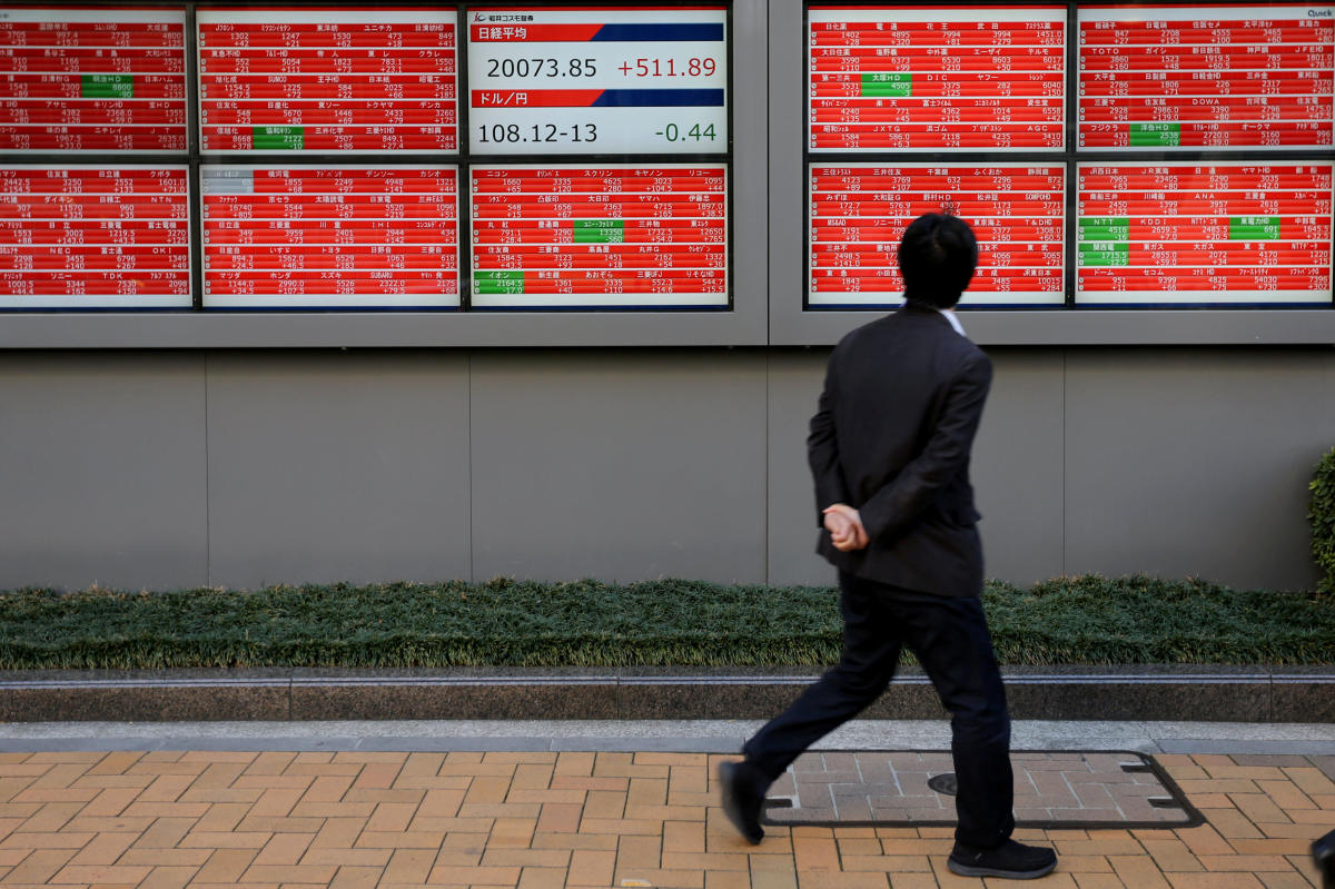A man looks at an electronic board showing the Nikkei stock index outside a brokerage in Tokyo, Japan. Reuters file photo.