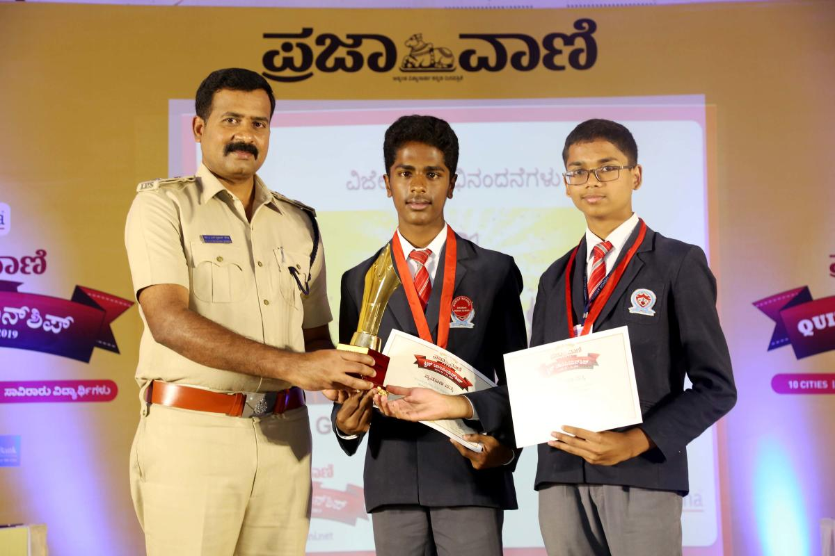 Proud Winners: Superintendent of Police A N Prakash Gowda presents prizes to winners of Prajavani zonal quiz championship, to Stevan and Jobin of Christ School, in Hassan on Wednesday. dh photo