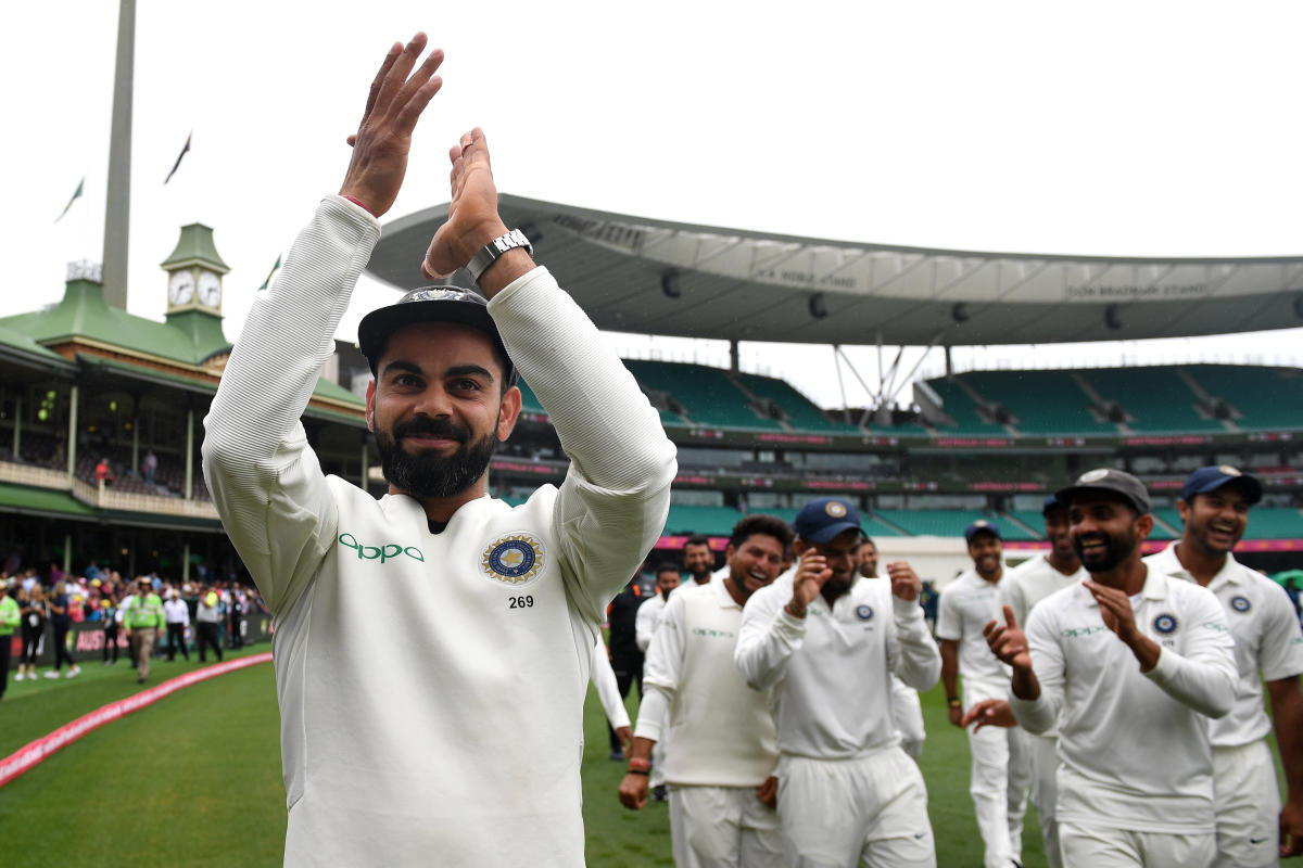 Virat Kohli gestures to supporters as his teammates celebrate a 2-1 series victory over Australia following play being abandoned on day five in the fourth test match between Australia and India at the SCG in Sydney. AAP/REUTERS