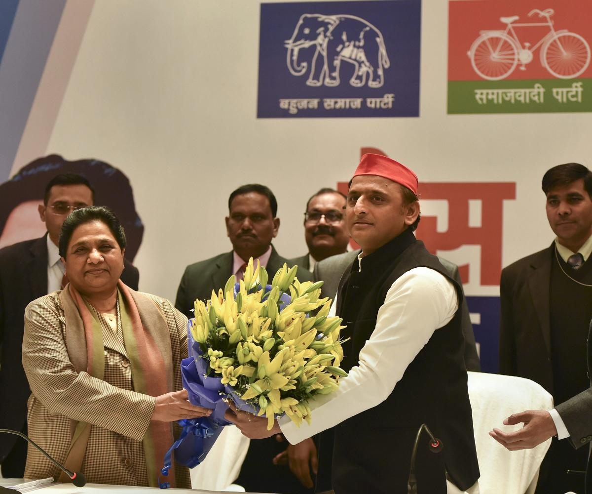 BSP supremo Mayawati being greeted with a bouquet by Samajwadi Party chief Akhilesh Yadav during a joint press conference in Lucknow. (PTI Photo)