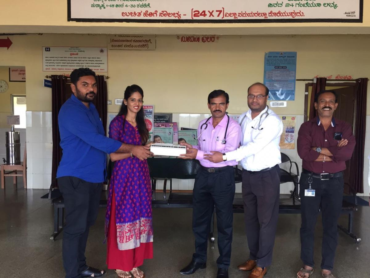 An ECG machine being handed over to Dr Shivakumar and Dr Madan Mohan at a CHC in Napoklu.