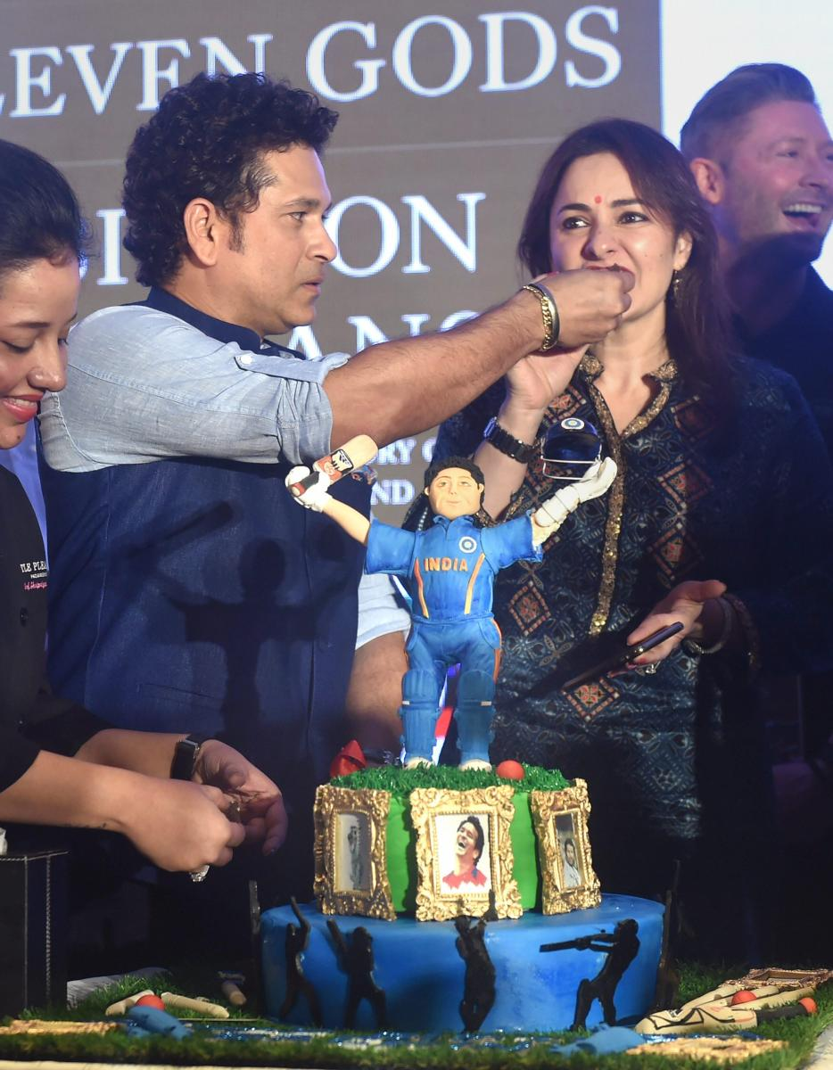 Cricket legend Sachin Tendulkar offers cake to his wife Anjali at a book launch function in Mumbai on the eve of his birthday on Monday. PTI