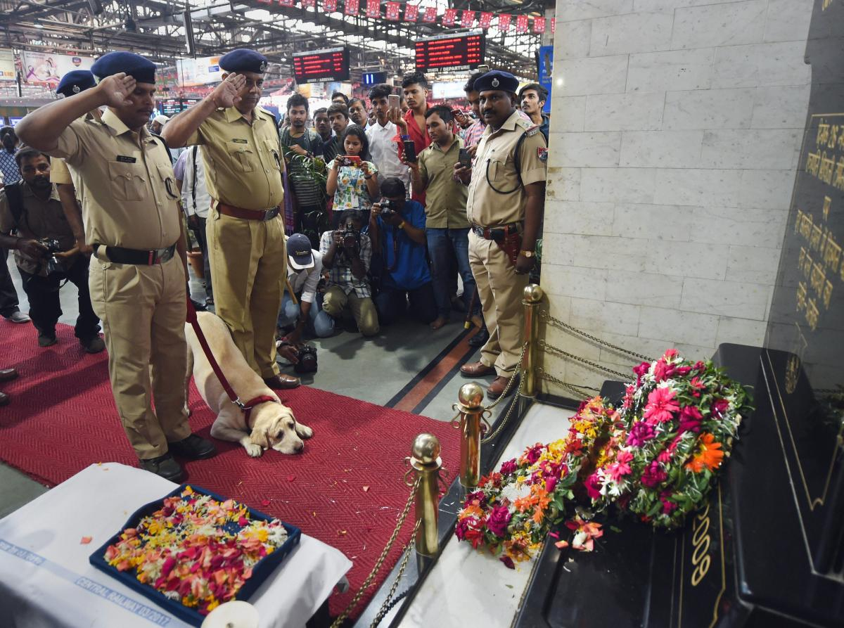 Dog squad members of the Railway police force pay tribute to victims of the 26/11 terror attack on its tenth anniversary, in Mumbai, Monday, Nov. 26, 2018. (PTI Photo)