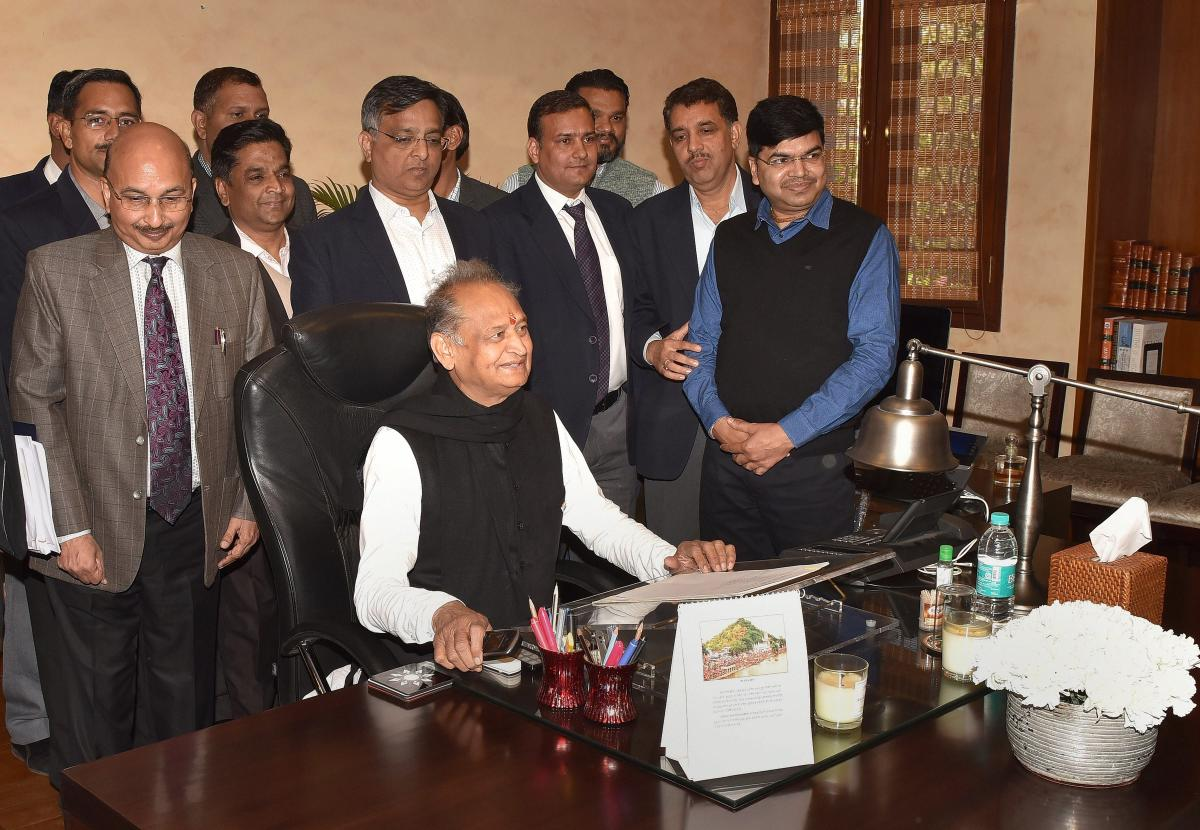Newly-elected Rajasthan Chief Minister Ashok Gehlot poses for a photo with CMO officials in Jaipur. (PTI Photo)