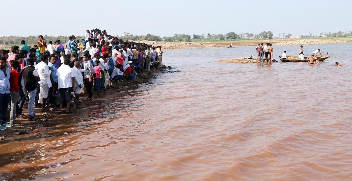 The police and expert swimmers attempt to retrieve bodies of two boys who drowned at Chikkasangam in Bilgi taluk, Bagalkot district, on Tuesday. DH Photo