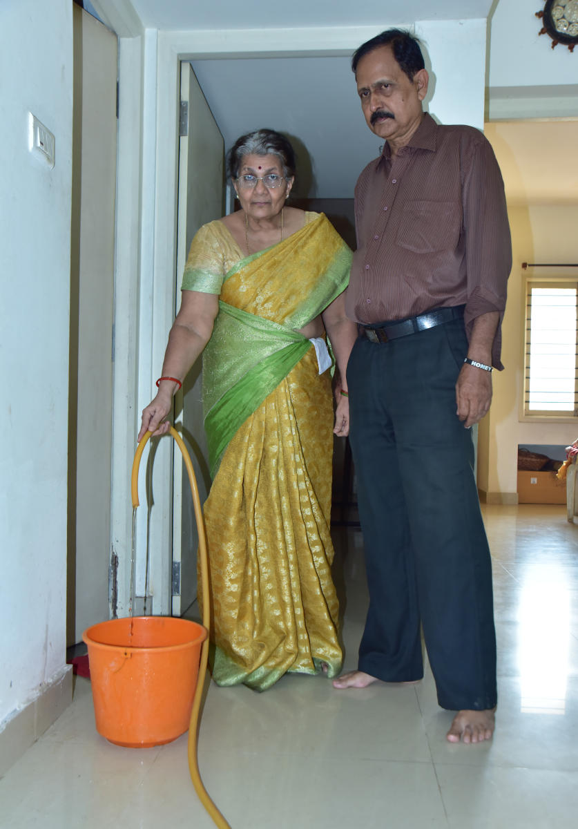 Elderly couple, Radhakrishna (68) and Shyamala (63), seen drawing water from the toilet for their cooking and other needs in their apartment in K2 Habitate apartment in Pandeshwar on Monday.