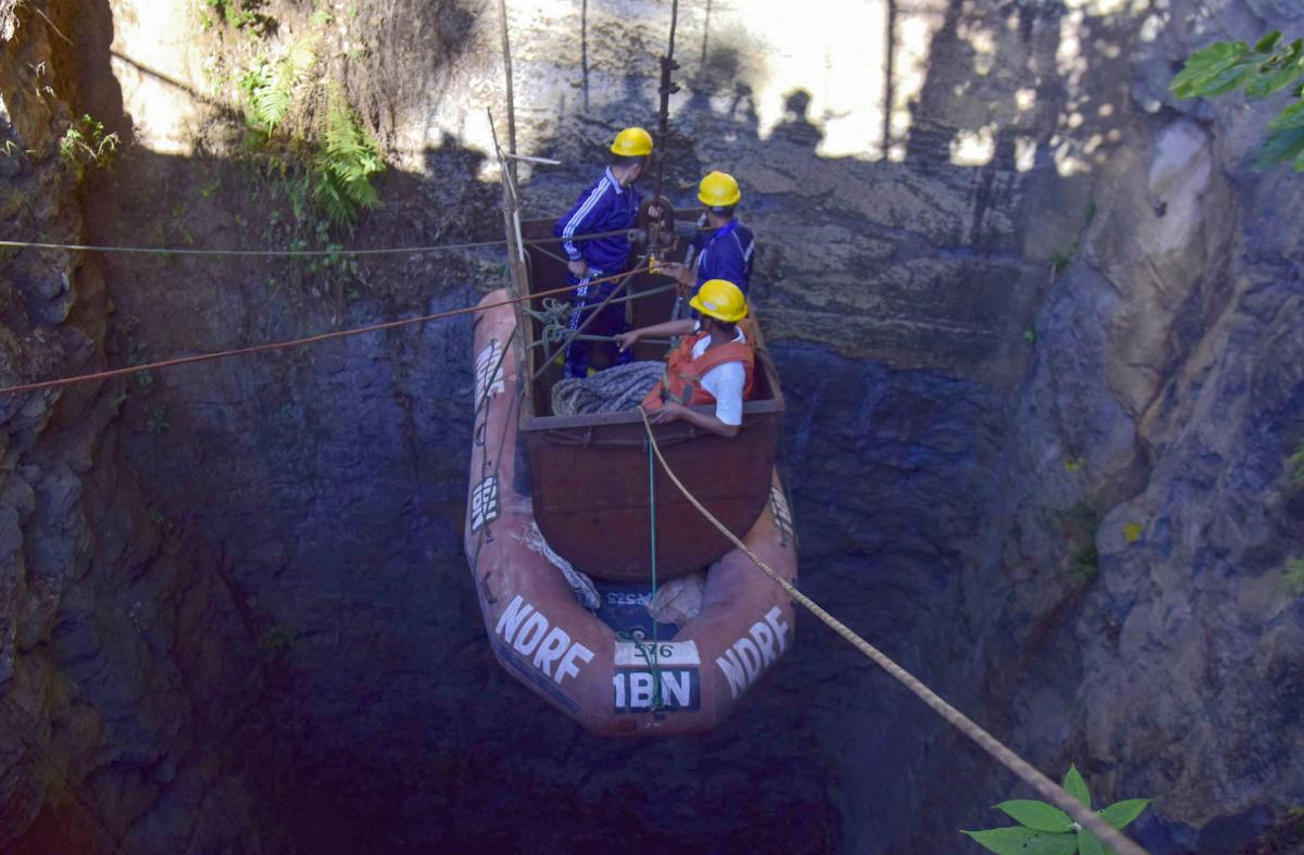 In this file photo taken on December 30, 2018 Indian Navy divers are lowered into a mine with a pulley during rescue operations to help 15 miners trapped by flooding in an illegal coal mine in Ksan village in Meghalaya's East Jaintia Hills district. AFP