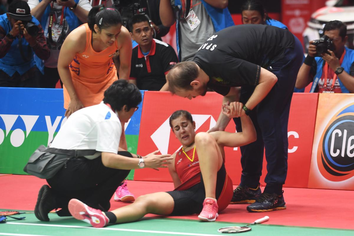 Carolina Marin of Spain (C) reacts to an injury that forced her to retire while playing against Saina Nehwal of India (top L) in their women's singles final match at the 2019 Daihatsu Indonesia Masters tournament in Jakarta on January 27, 2019. (AFP)