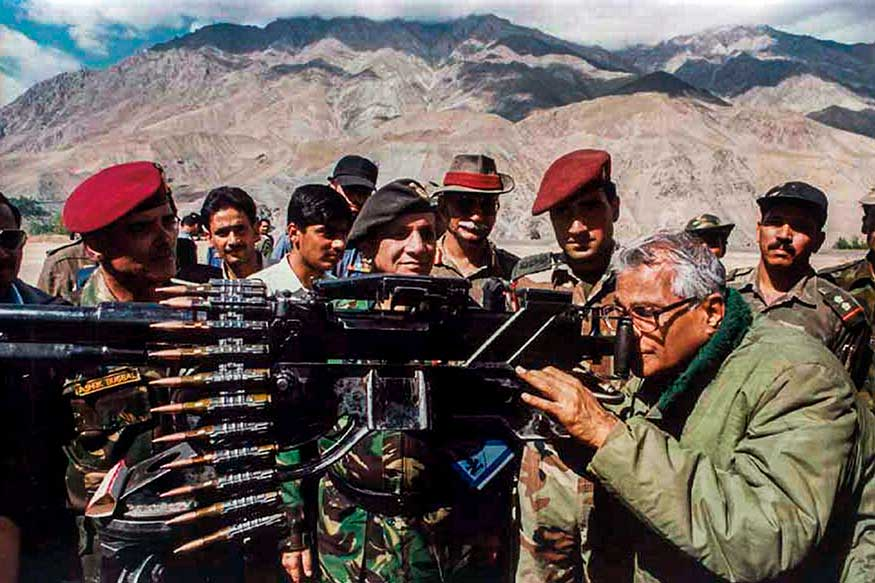 George Fernandes taking a view through a heavy machine gun, seized from the Pakistan army in Kargil. (Image: PTI)