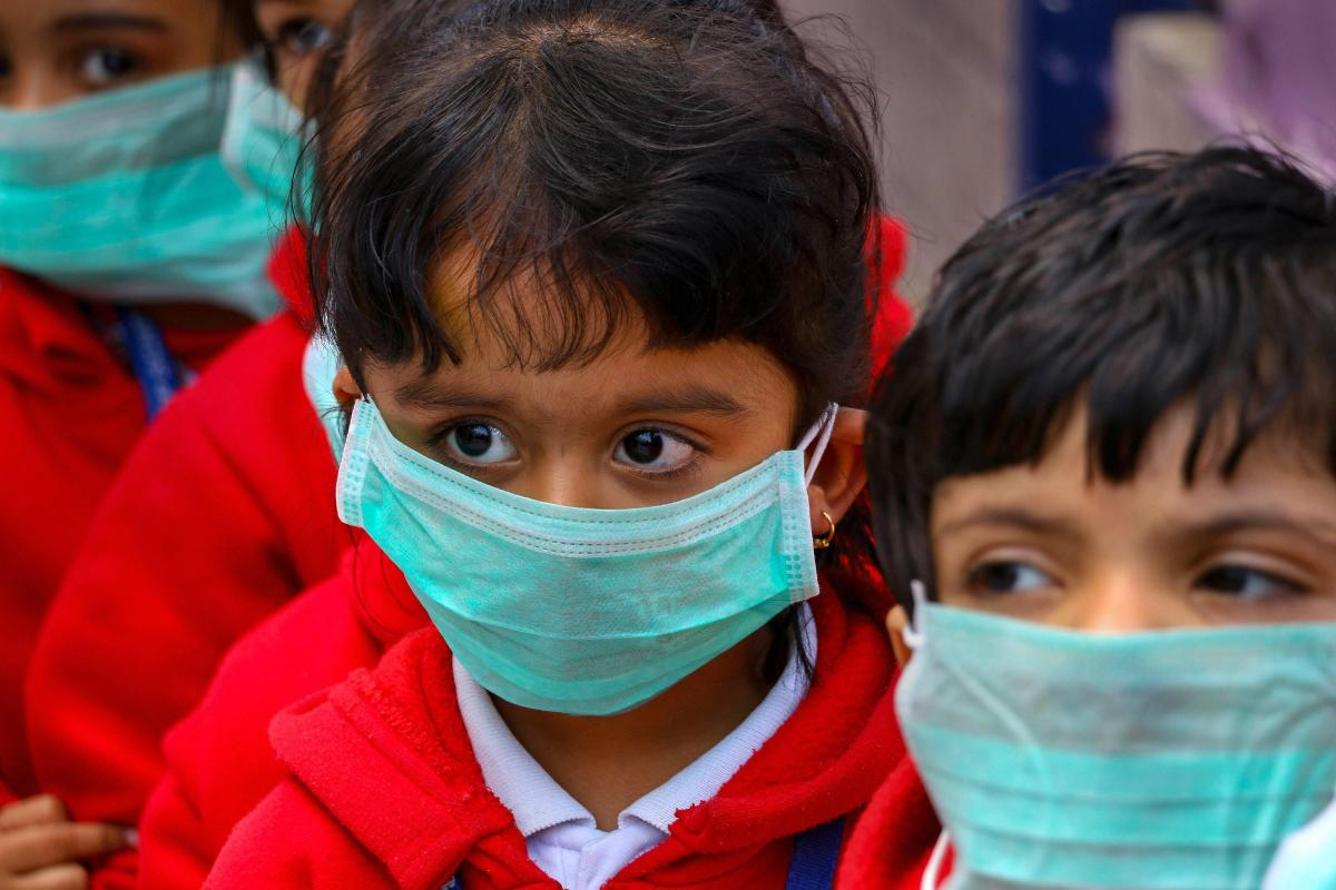 Students, wearing masks as protection against Swine Flu, attend a class at a school in Ajmer, Wednesday. PTI photo