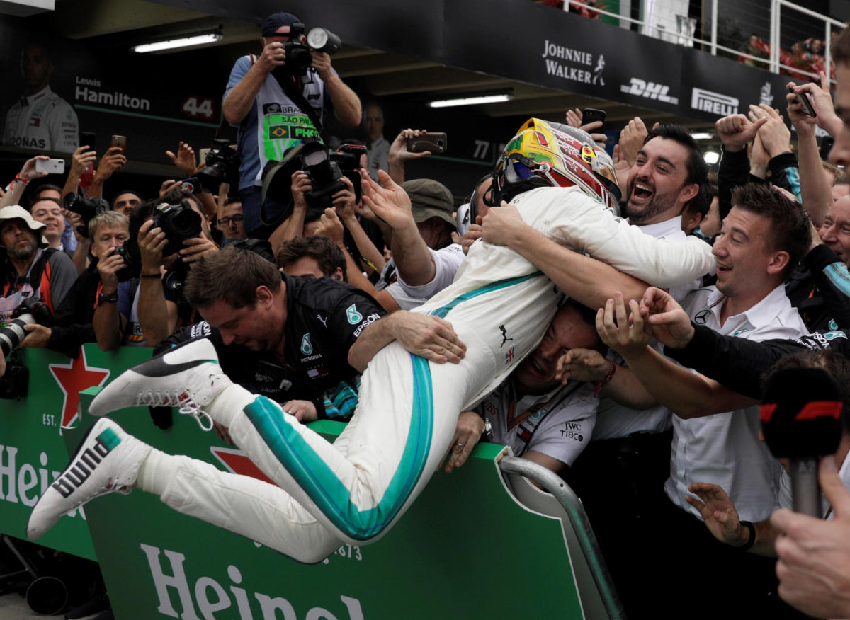 Mercedes' Lewis Hamilton celebrates with team members after winning the race. Reuters