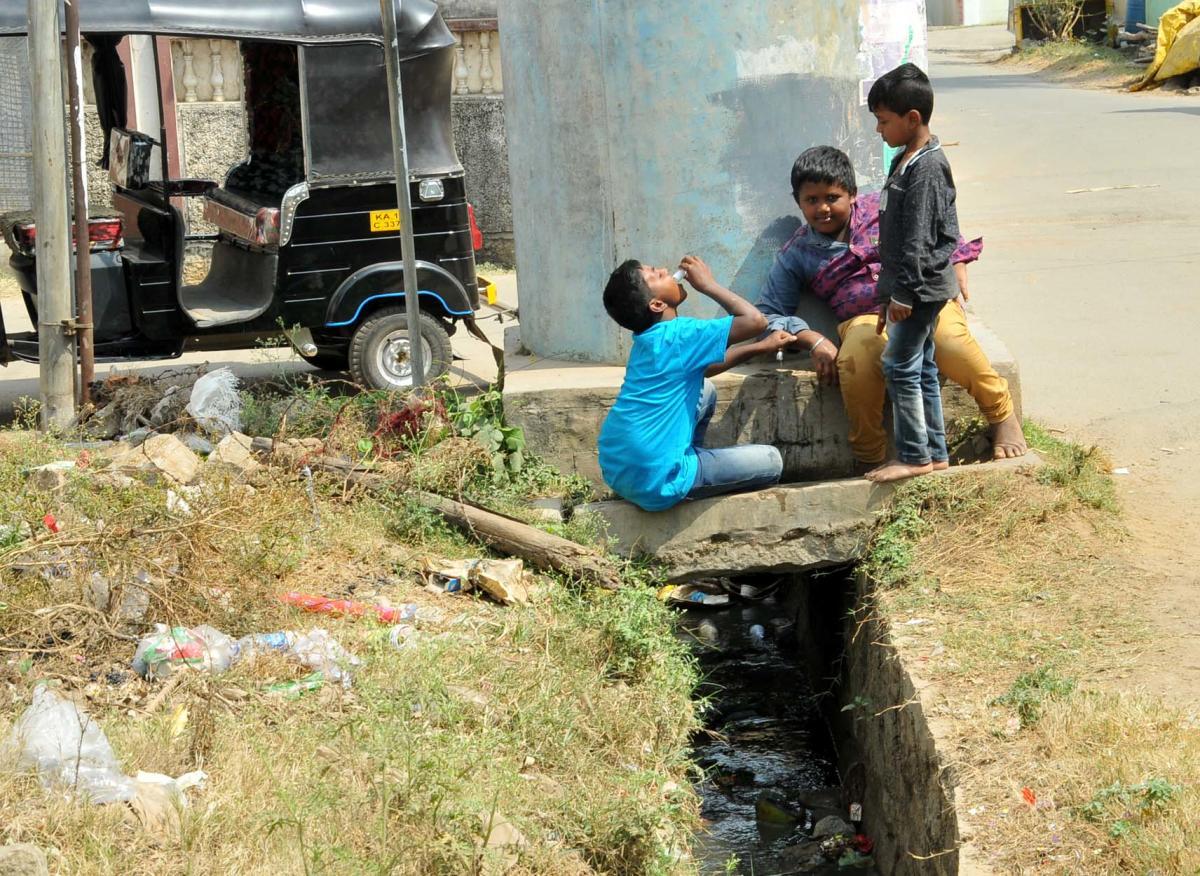 Children play beside a drain in Chikkamagaluru.