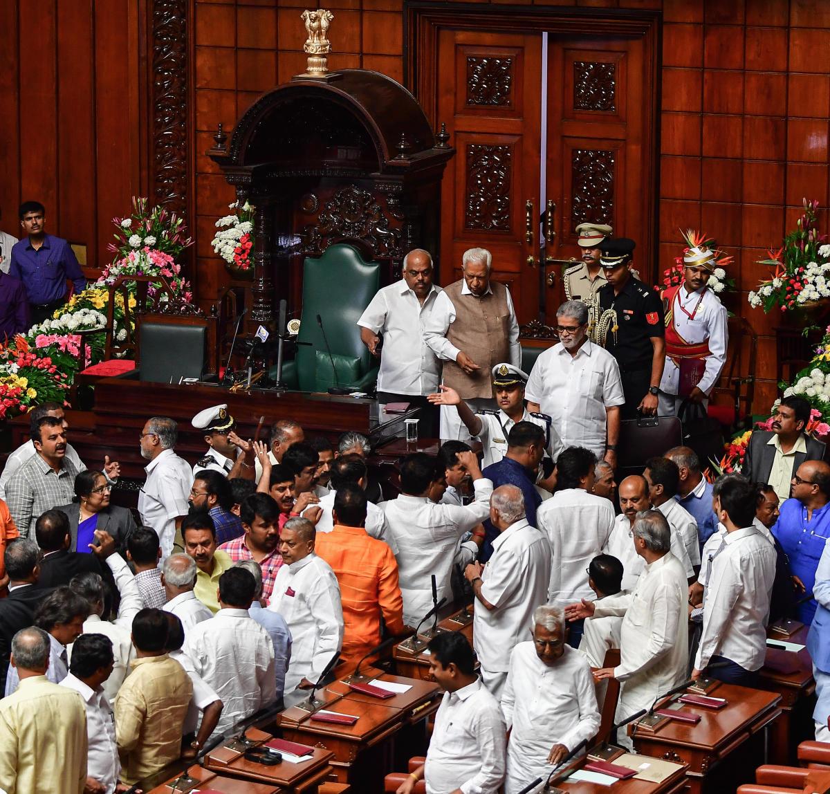 Governor Vajubhai Vala walks out as Opposition BJP members disrupt his address to the joint legislature session on Wednesday. Legislative Assembly Speaker K R Ramesh Kumar and Legislative Council Chairman K Prathap Chandra Shetty are seen. DH photo
