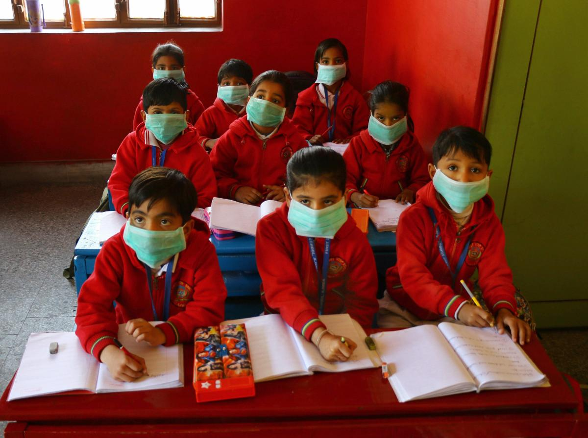 Students, wearing masks as protection against Swine Flu, attend a class at a school. PTI file photo for representation.