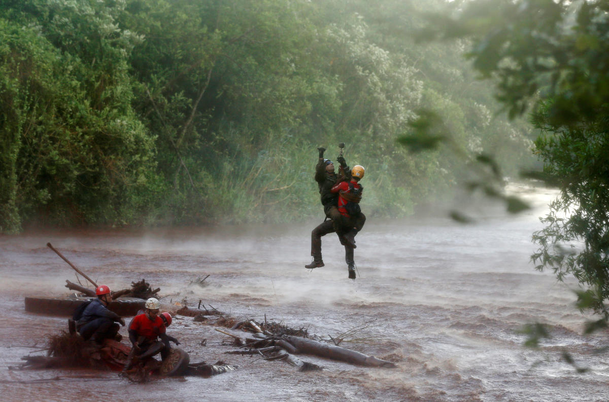 A soldier helps a member of a rescue team on Paraopeba River as they search for victims of a collapsed tailings dam owned by Brazilian mining company Vale SA, in Brumadinho, Brazil February 5, 2019. REUTERS