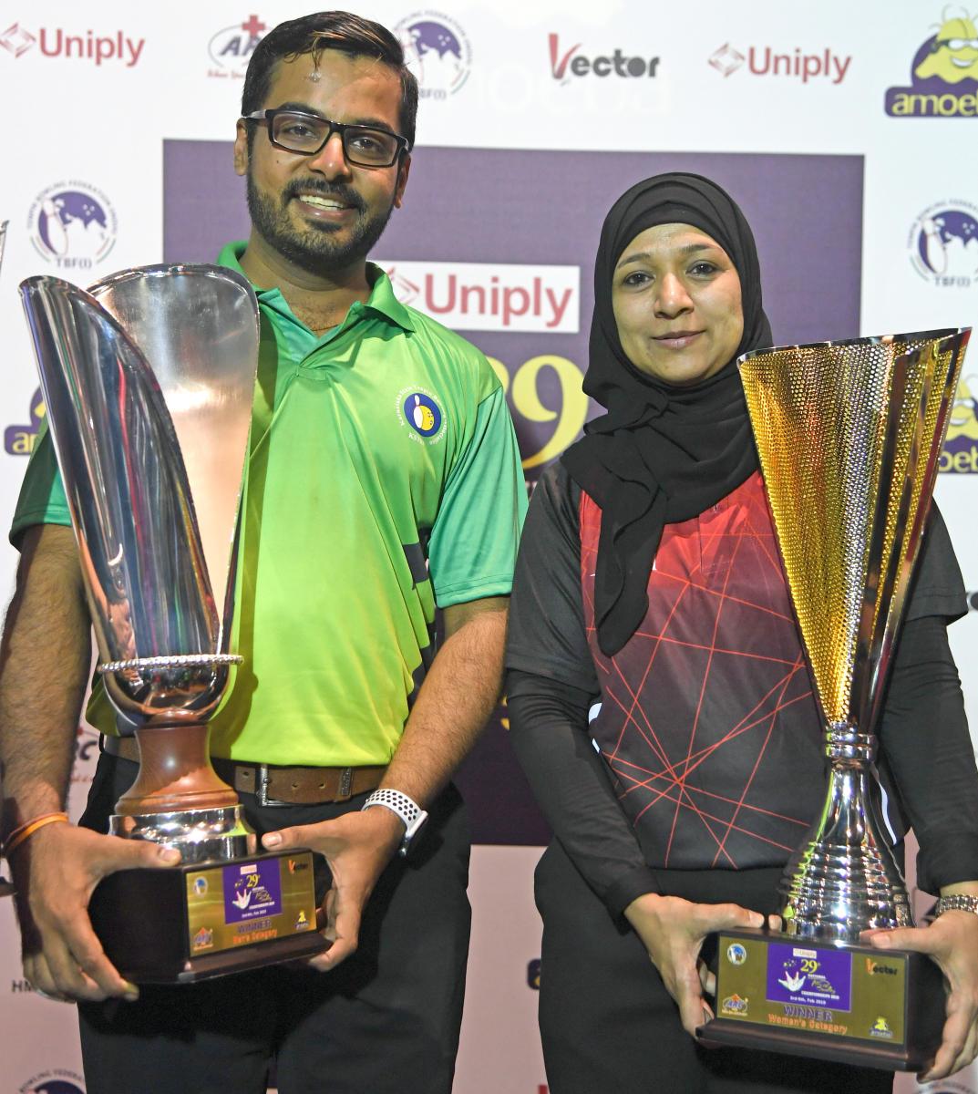 Karnataka's Akaash Ashok Kumar (left) and Sabeena Athica of Tamil Nadu with their trophies in Bengaluru on Saturday. DH PHOTO