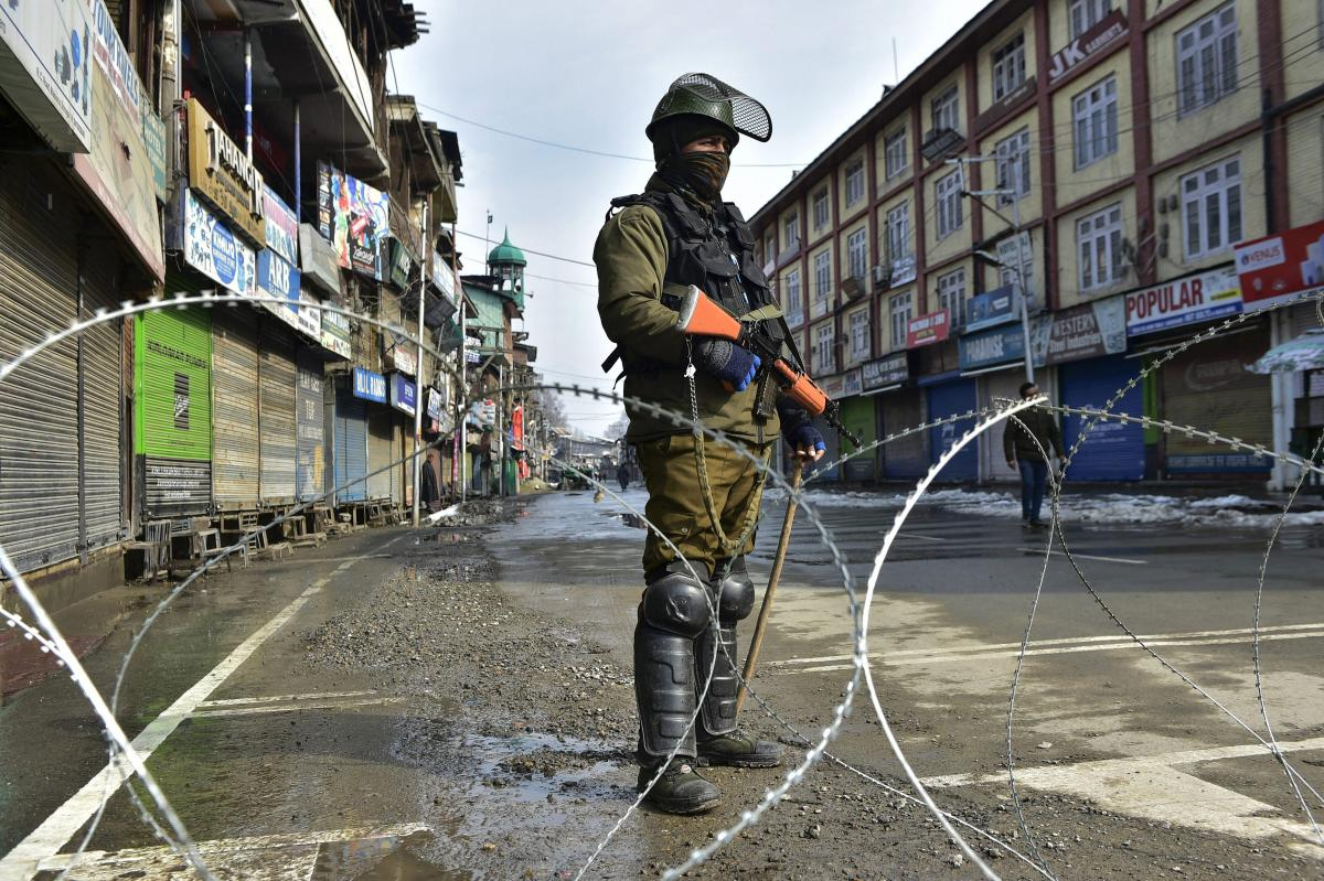 A security personnel stands guard along a barbed wire during a strike called by separatist leaders to mark the 35th death anniversary of Jammu and Kashmir Liberation Front (JKLF) founder Mohammad Maqbool Bhat, in Srinagar on Monday. PTI