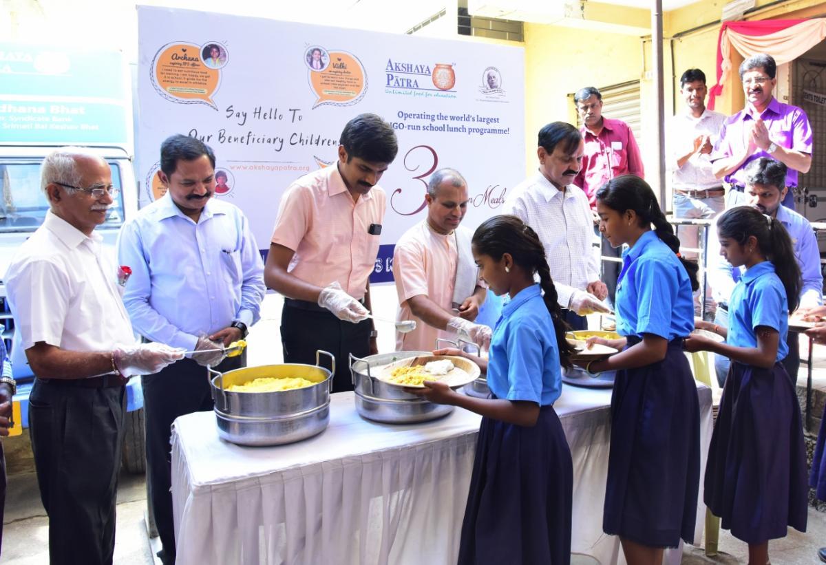 Deputy Commissioner Abhiram G Sankar serves hot food to students, during a programme, in Mysuru on Monday.