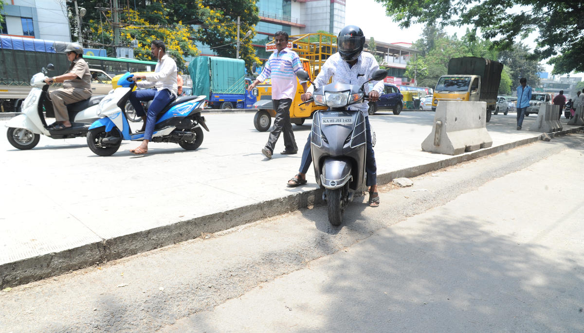 A motorist struggles to get onto the asphalted road from the half complete white-topped pavement on Mysore Road on Saturday. Photo Srikanta Sharma R.