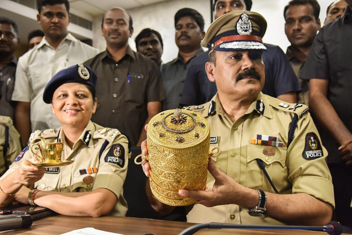 Police Commissioner Anjani Kumar along with a senior police officer shows the three-tier golden tiffin box and a golden cup after their recovery, in Hyderabad on Tuesday. PTI