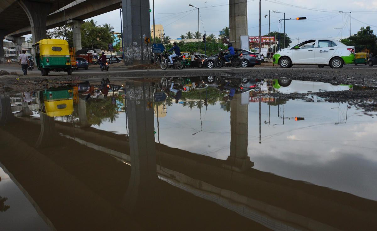 Rainfall has heavily damaged the road at Nayandahalli Circle. DH PHOTO/RANJU P
