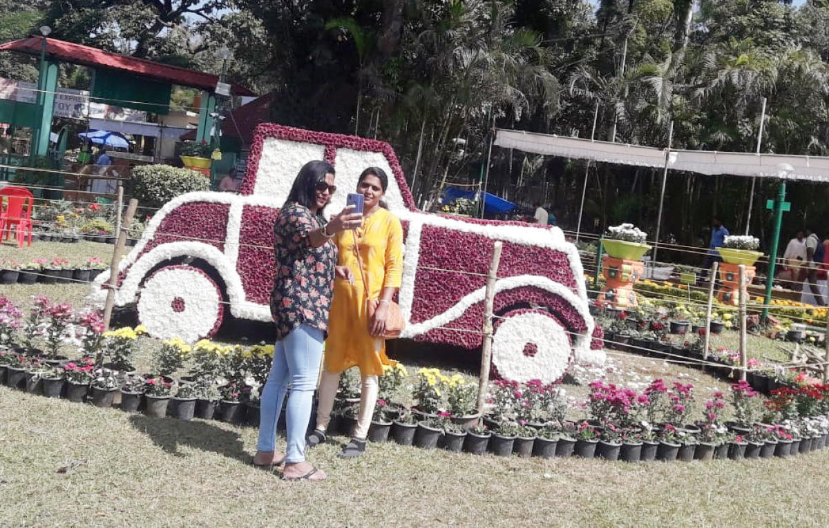 A woman clicks a selfie at the flower show at Raja Seat in Madikeri.