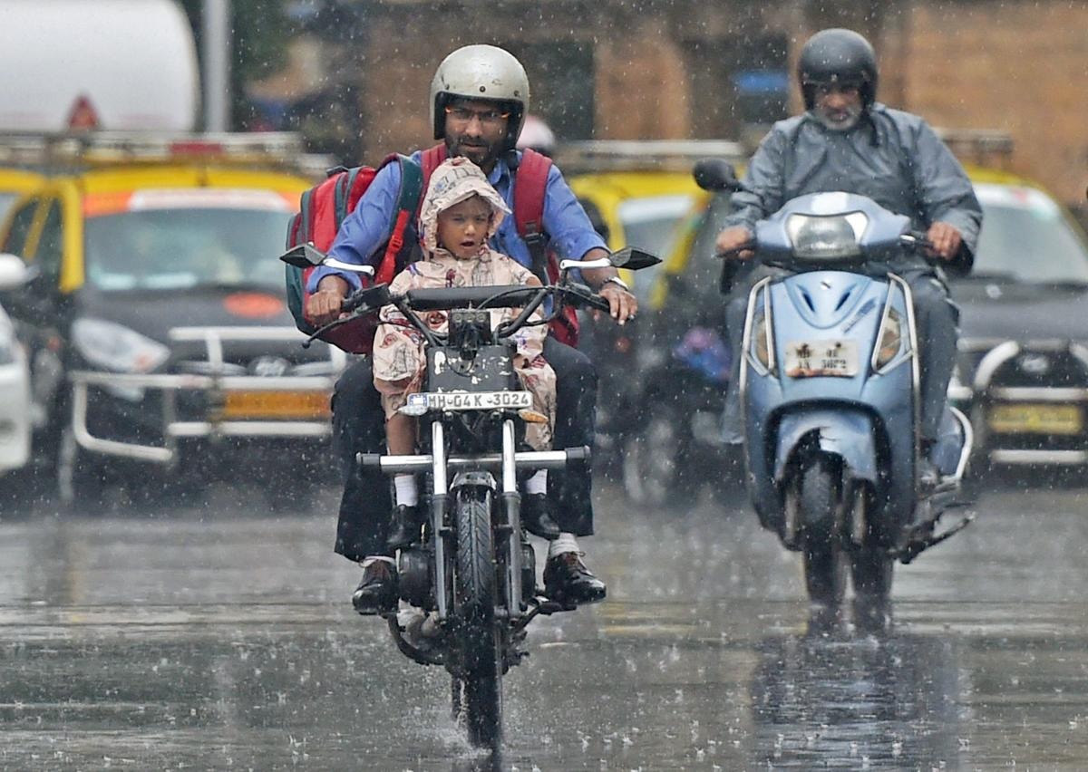 A man carries his child home from school on a motorcycle amid a downpour in Mumbai on Tuesday. PTI