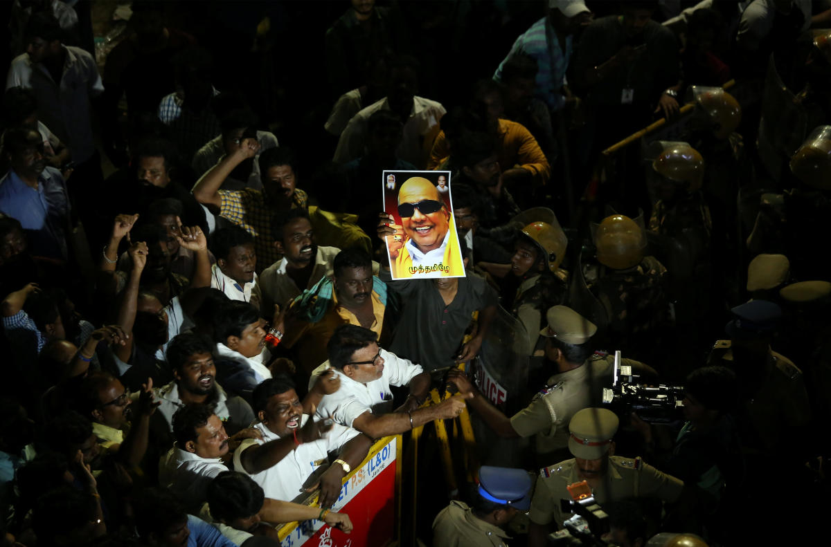Supporters gather as an ambulance carrying the remains of Indian Tamil leader M. Karunanidhi leaves the hospital in Chennai, India August 7, 2018. (REUTERS/P. Ravikumar)