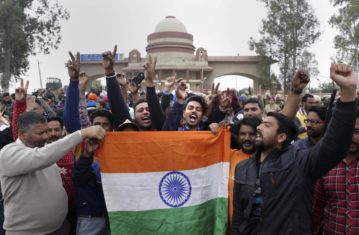 Attari: People jubilate with a Tricolour as they wait for the arrival of IAF pilot Wing Commander Abhinandan Varthaman at Attari-Wagha border near Amritsar, Friday, March 1, 2019. Varthaman, who was captured by Pakistan after his jet went down following a strike by an enemy missile, is expected to be released today. (PTI Photo)