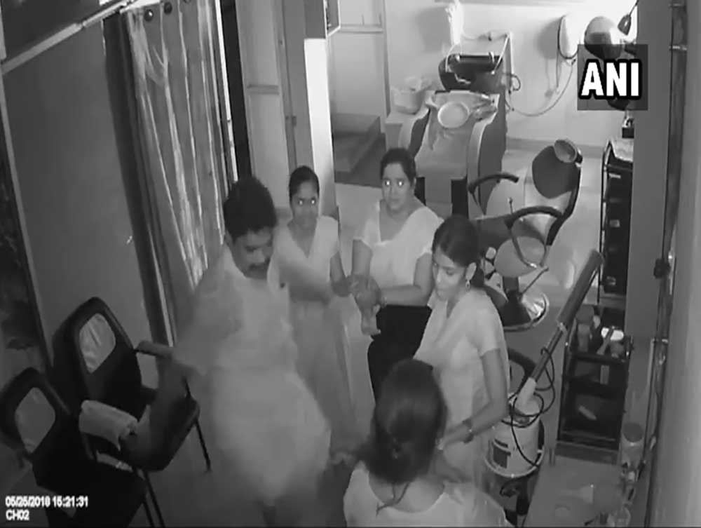 In the short video which went viral Thursday, the man clad in a white shirt and dhoti is seen repeatedly kicking the woman and pushing her down in the parlour in Perambalur, about 300 km from here. Image courtesy ANI/Twitter