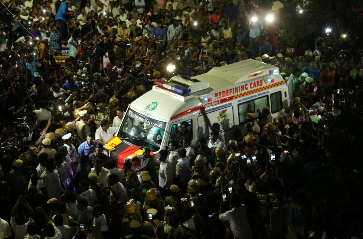 Supporters gather as an ambulance carrying the remains of Indian Tamil leader M. Karunanidhi. PTI Photo