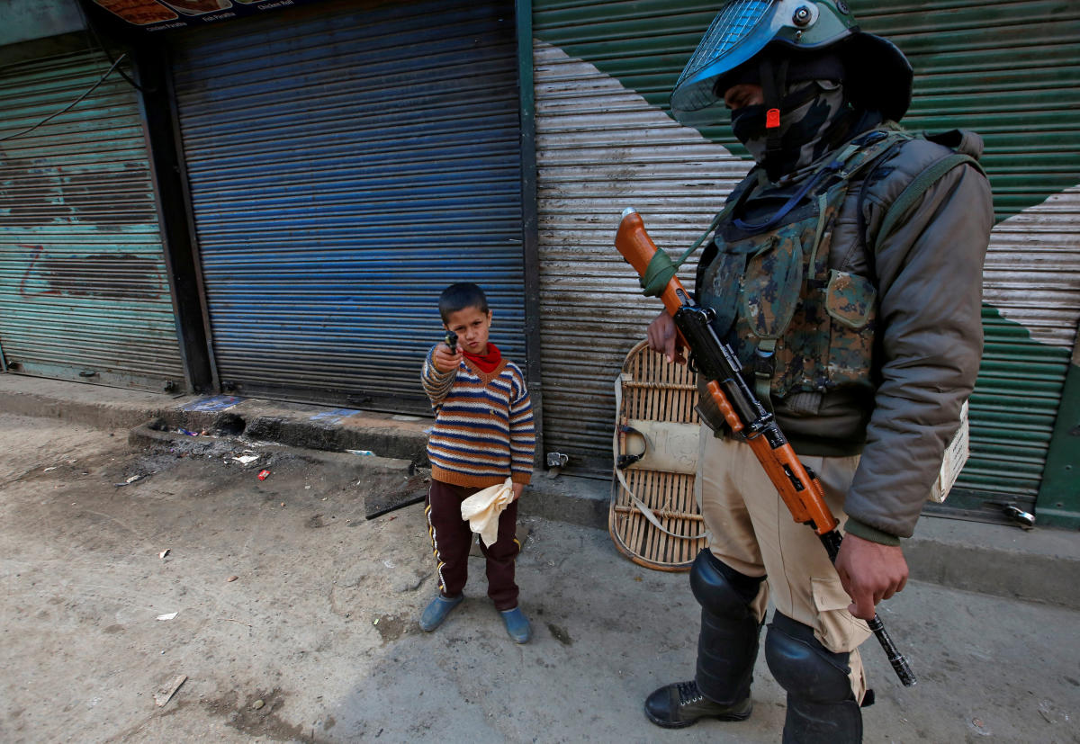 A boy plays with his toy pistol next to an Indian policeman standing guard in front of closed shops during a strike called by Kashmiri separatists against the arrest of Yasin Malik in Srinagar. Reuters photo