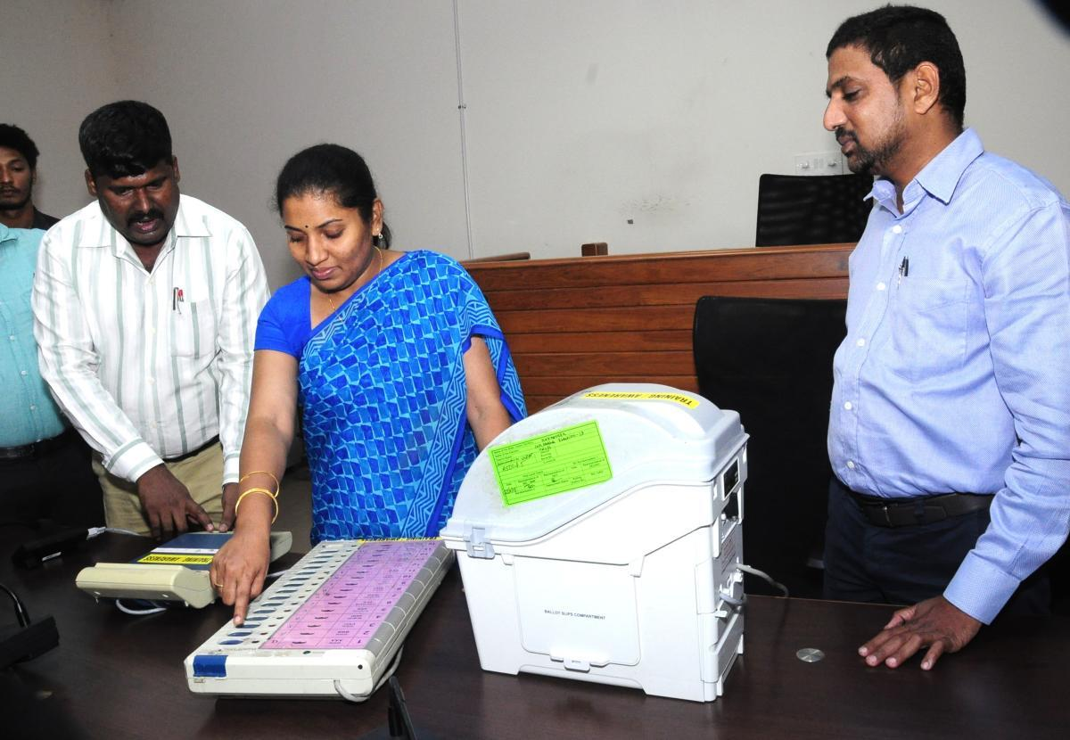 Deputy Commissioner Hephsiba Rani Korlapati demonstrates the working of an EVM and VVPAT at Udupi.